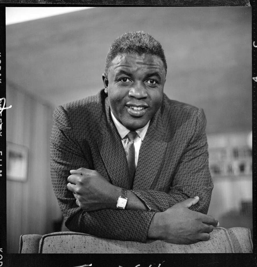 American professional baseball player Jackie Robinson, who famously broke the Major League Baseball color barrier in 1947 leans on the back of a chair as he appears at his home for the CBS television program 'Person to Person' shortly after announcing his retirement from baseball, Stamford, Connecticut, January 21, 1957. Photo: CBS Photo Archive, File / 2006 CBS WORLDWIDE INC.
