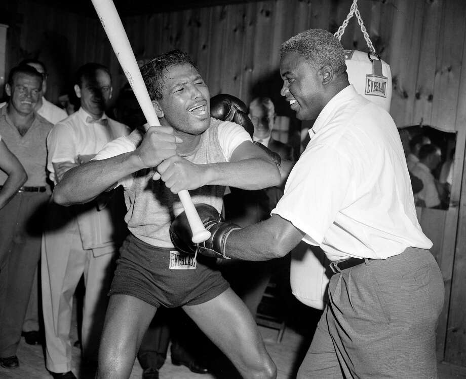 Middleweight boxing champ Sugar Ray Robinson, left, playfully wields a bat to fend off blows from the gloved fists of former baseball legend Jackie Robinson, at the boxer's training camp in Greenwood Lake, N.Y., Sept. 12, 1957.  Jackie Robinson is now an executive with a restaurant chain.  (AP Photo) Photo: File