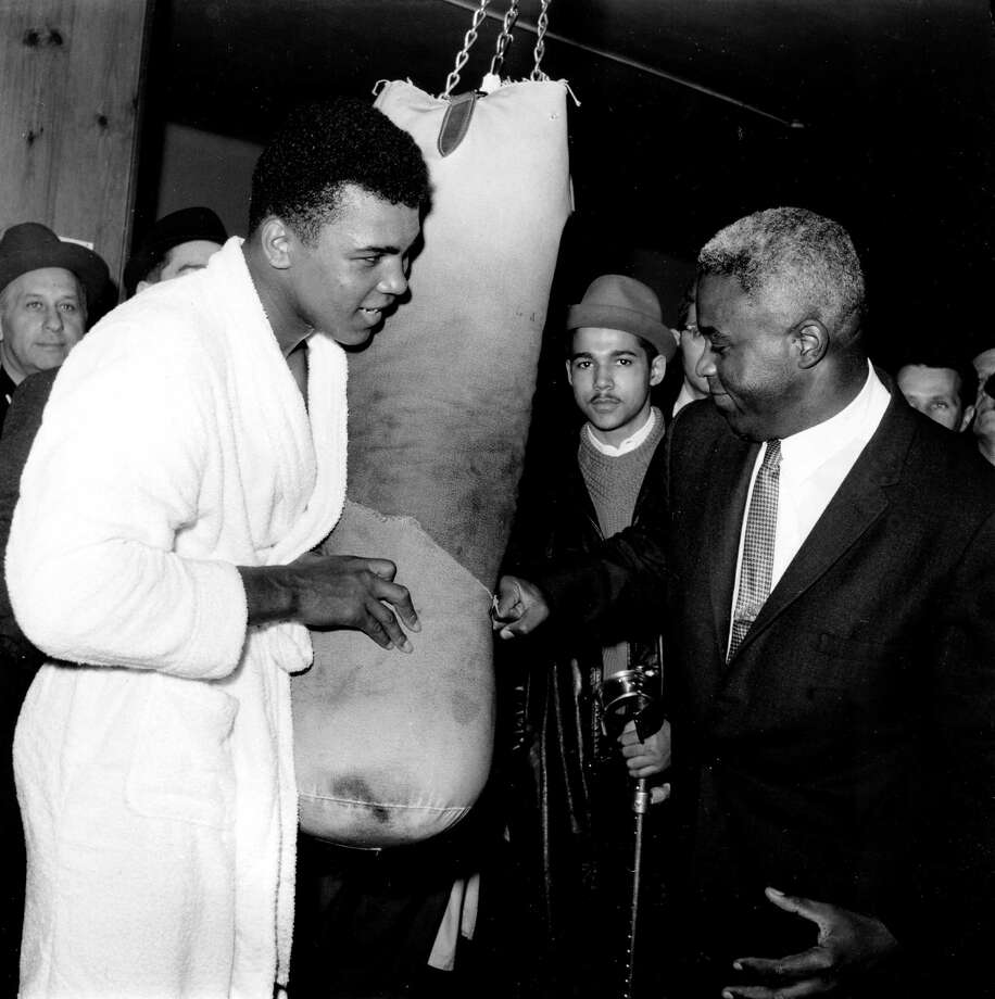 Jackie Robinson, former Brooklyn Dodgers baseball player, hits a punching bag held by heavyweight boxing champion Cassius Clay in a New York gym during his visit on March 13, 1963.  (AP Photo) Photo: File / AP1963