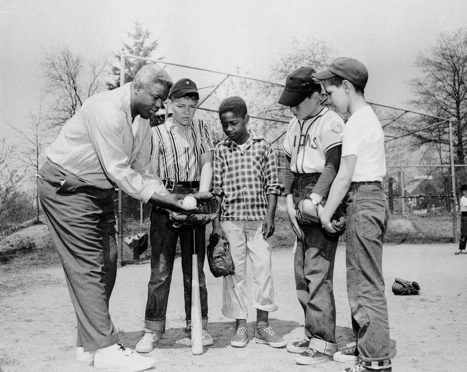 Former Brooklyn Dodger Jackie Robinson gives instructions to his son Jackie Jr., and his teammates of his little league team in Stamford, Conn., on April 27, 1957.  (AP Photo) Photo: Anonymous, File / AP1957