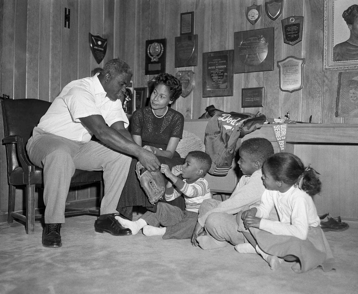 Baseball player Jackie Robinson sits with his wife Rae and their children, David, 4, Jackie Jr., 10, and Sharon, 7, in the trophy-decorated den of their home, in Stamford, Conn., Jan. 6, 1957. (AP Photo/Harry Harris)
