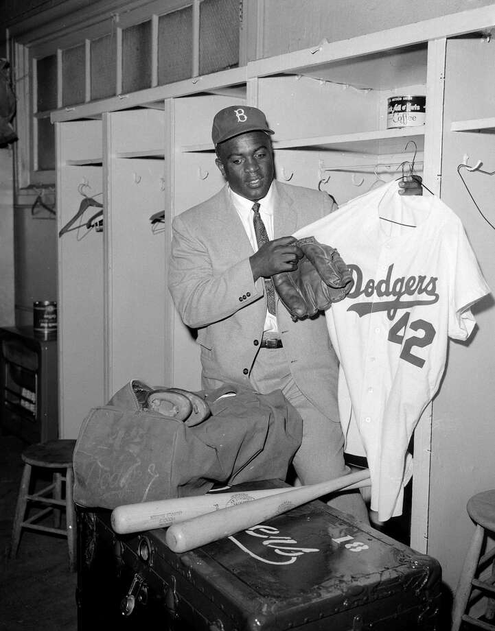 Brooklyn Dodgers' legend Jackie Robinson clears out his locker at Ebbets Field, Jan. 7, 1957, after ten years with the ball club.  Robinson quit baseball after it was announced he would be traded to the New York Giants, and will work as an executive with the Chock Full O' Nuts company.  He said he made the decision in the interest of the security of his family.  (AP Photo/Jack Harris) Photo: File