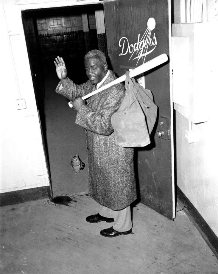 Jackie Robinson, who has retired after a 10-year career, waves as he leaves the clubhouse after collecting his belongings at Ebbets Field in Brooklyn, N.Y., on Jan. 7, 1957.  Robinson, 38, became the first black baseball player in the modern major leagues when he joined the Brooklyn Dodgers in 1947.  (AP Photo/Jacob Harris) Photo: File