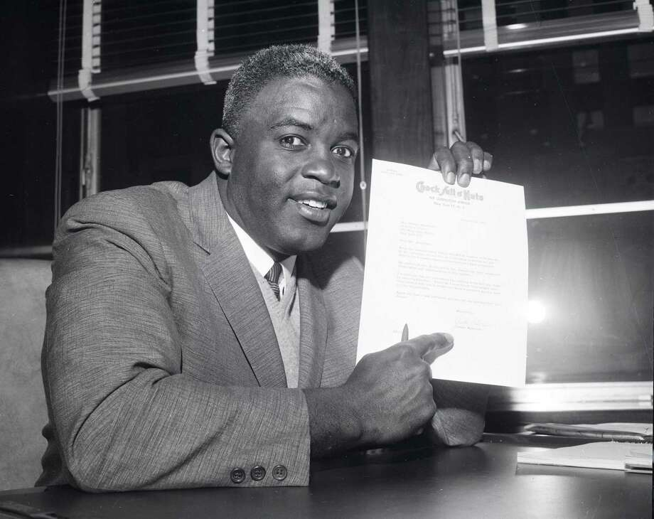 Jackie Robinson shows the letter which announces his retirement from baseball in January, 1957 in the Brooklyn borough of New York City. Photo: Transcendental Graphics, File / 1957 Transcendental Graphics