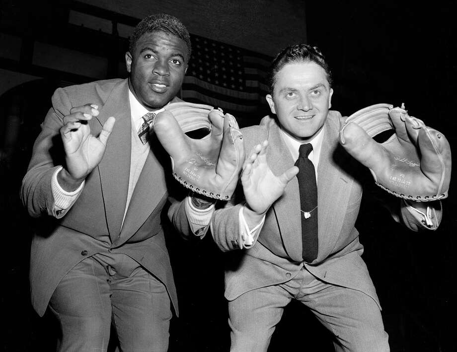 "Jackie Robinson of the Brooklyn Dodgers, left, and Willard Marshall of the Boston Braves demonstrate the ""Big Mitt"" fielding form that put them into the baseball record books during a get-together in New York, Dec. 18, 1951.  (AP Photo/Harry Harris) Photo: File"