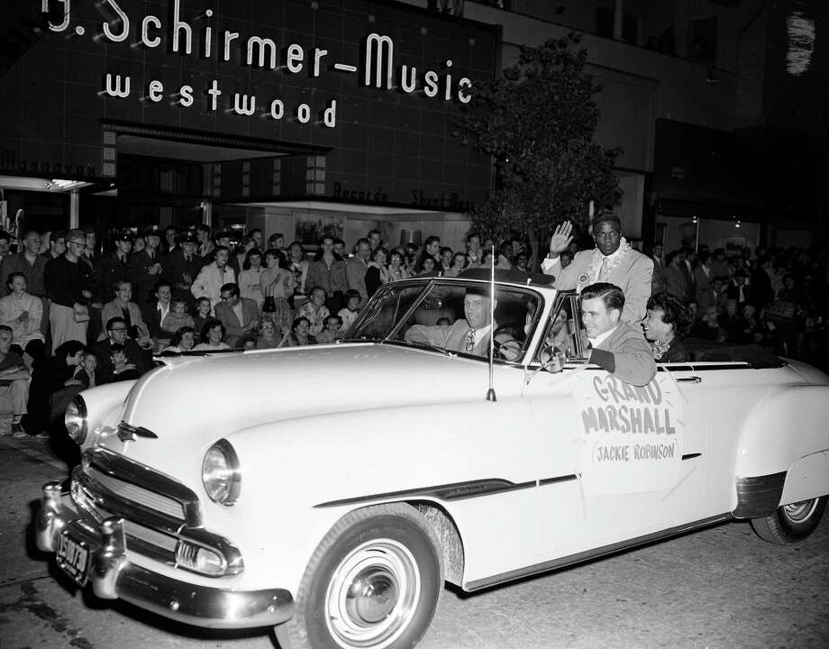 Brooklyn Dodgers star and parade grand marshall Jackie Robinson waves to the crowd at the UCLA homecoming parade, Nov. 2, 1951 in Los Angeles.  Robinson is an alumnus of UCLA where he starred in football, baseball and track. His wife Rachel is seen beside him.  Others are unidentified.  (AP Photo/Ed Widdis) Photo: File