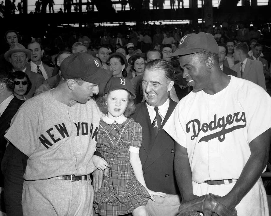 Kathleen Dugan, 5-year-old who had been a polio victim, sold the first ticket to the Jackie Robinson-Joe DiMaggio dinner to Commissioner A. B. Chandler during the fifth World Series game Ebbets Field in New York, Oct. 9, 1949. At the commissioner's box are, left to right, Tommy Henrich of the Yankees; Kathleen; Chandler; and Jackie Robinson of the Dodgers.  (AP Photo/Dan Grossi) Photo: Dan Grossi, File / AP