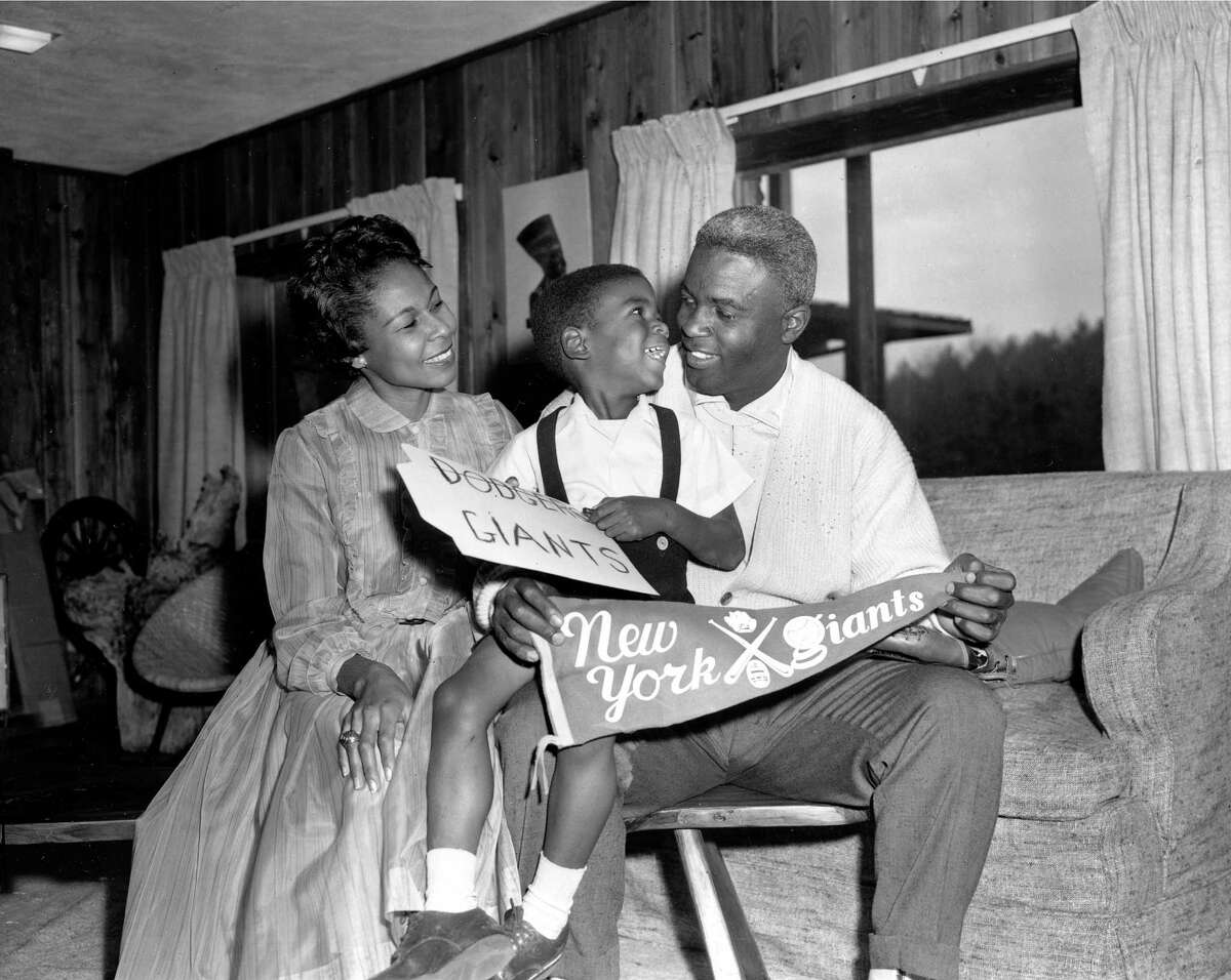 Jackie Robinson, Brooklyn Dodgers star since breaking into Major League baseball in 1947, is shown with his wife, Rachel, and their four-year-old son, Jackie Jr., in their home in Stamford, Conn., Dec. 13, 1956. Robinson, 37, holds a banner for the rival New York Giants baseball club to which he was traded for relief pitcher Dick Littlefield and $35,000 in cash. Robinson retired in January, voiding the trade. (AP Photo/John Lindsay)