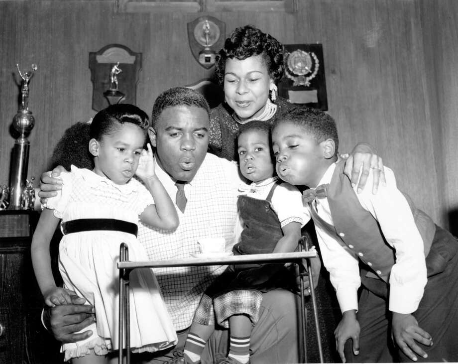 Jackie Robinson's wife and children gather close to help him blow out the candle on a cupcake as they celebrate the Brooklyn Dodgers infielder's 35th birthday at home in St. Aldans, N.Y. on Jan. 31, 1954.  From left are, Sharon, 4; Jackie, with David, 20 months, on his knee;  his wife, Rachel; and Jackie Jr., 7.  (AP Photo) Photo: File / AP1954