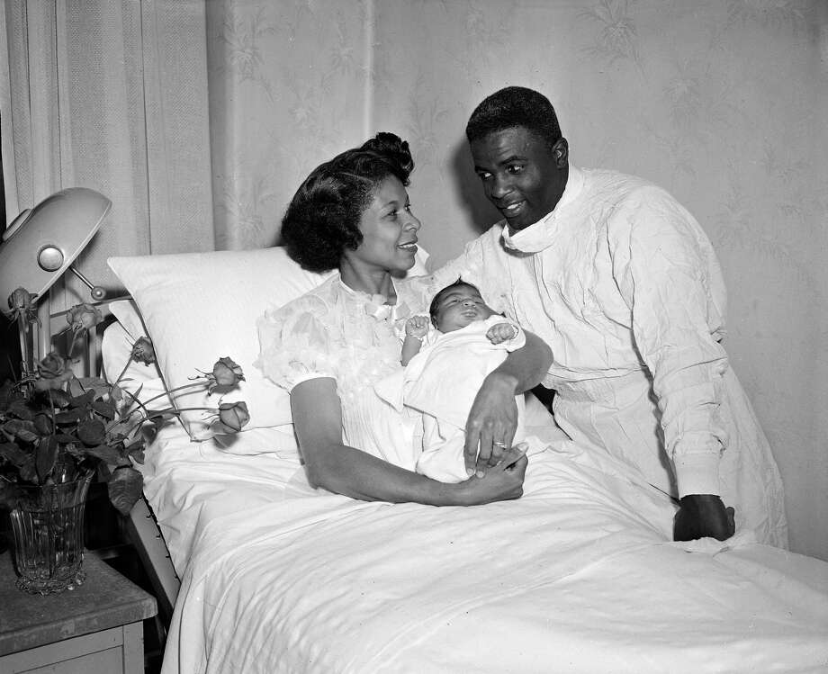 Baseball legend Jackie Robinson looks at this wife Rachel as she holds their second son, David, at Flower Fifth Avenue Hospital in New York, May 15, 1952.  The baby was born yesterday.  The Robinsons also have a daughter, Sharon, and a son, Jackie Jr.  (AP Photo/John Rooney) Photo: JOHN ROONEY, File / AP1952