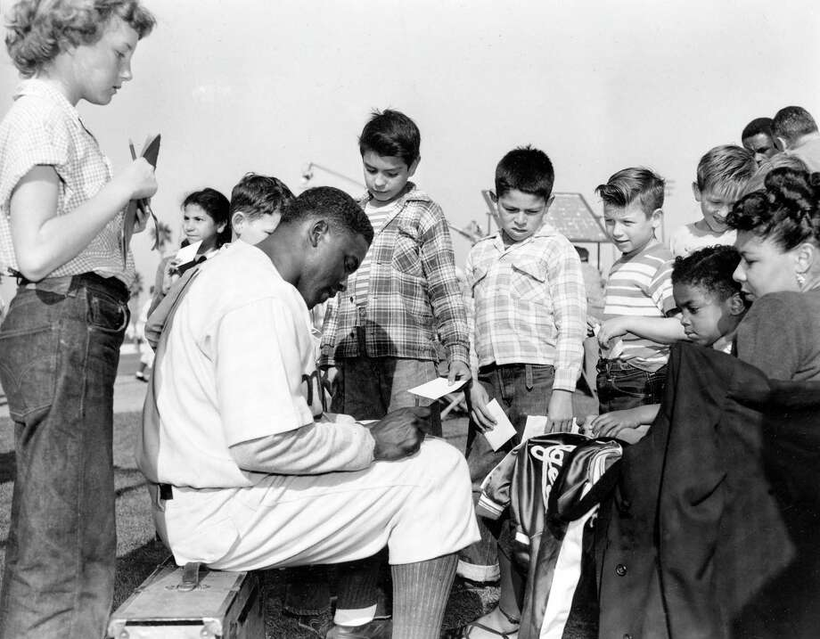 With his wife Rachel and his son looking on at right, Brooklyn Dodgers' first baseman Jackie Robinson signs autographs for his young fans, in Anaheim, Calif., on February 20, 1950. (AP Photo) Photo: File / AP1950