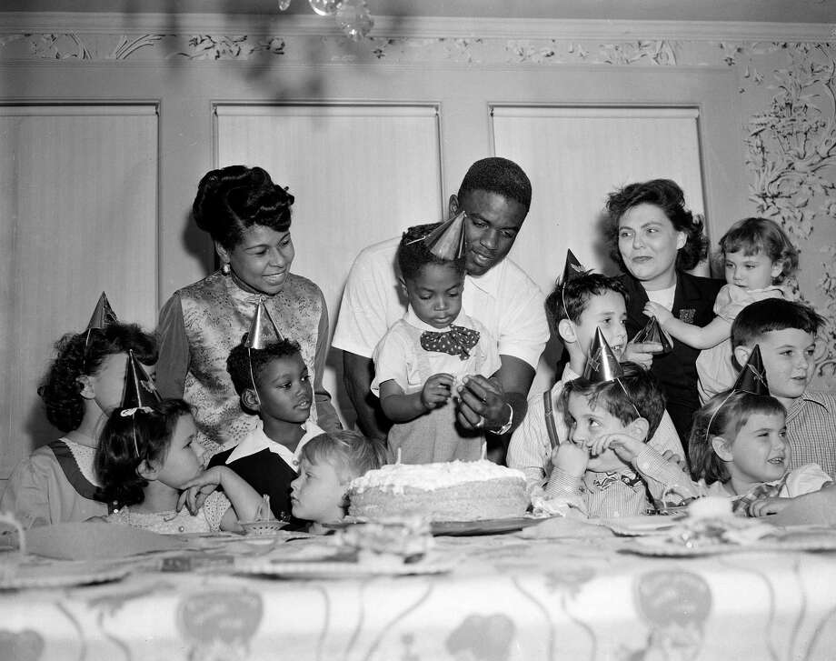 Young guests surround Brooklyn Dodgers' second baseman Jackie Robinson and his son Jackie Jr. as they light candles on his birthday cake for his third birthday party in St. Albans in the Queens section of New York, Nov. 18, 1949.  Jackie Sr. was also named Most Valuable Player in the National League today.  At left is Rachel Robinson, the baseball star's wife, and at right is Sarah Satlow, his secretary.  Other children are unidentified.  (AP Photo/John Rooney) Photo: File
