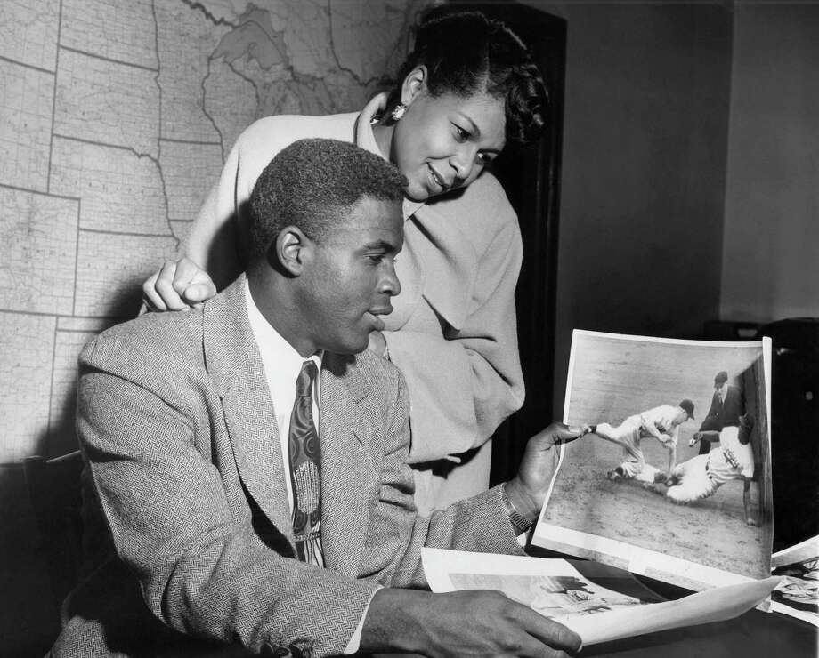 Jackie Robinson, Brooklyn Dodger second baseman, and his wife, view an action picture of the ball player in New York on Nov. 17, 1949. Robinson was named most valuable player in the National League on the basis of his 1949 record. Robinson, first member of the African American race to win this honor in modern major league baseball, polled 12 of 24 firsts, in the competition conducted by 24 members of the Baseball Writers Association, three from each major league city. (AP Photo/Marty Lederhandler) Photo: File