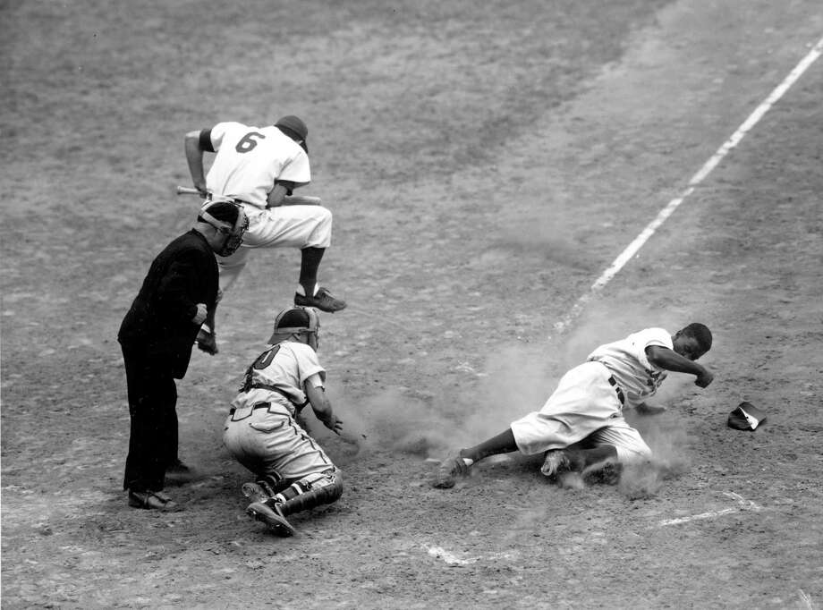 Jackie Robinson, second baseman of the Brooklyn Dodgers, steals home in the fifth inning against the Boston Braves at Ebbets Field in Brooklyn, N.Y., on Sept 28, 1948.  Robinson beat pitcher Warren Spahn's throw to catcher Phil Masi.  Dodger Carl Furillo (6) leaps out of the way as umpire George Barr calls the play.  (AP Photo) Photo: File