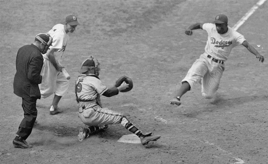 FILE -- Brooklyn Dodgers Jackie Robinson, steals home plate as Boston Braves' catcher Bill Salkeld is thrown off-balance on pitcher Bill Voiselle's throw to the plate during the fifth inning at Ebbets Field in New York August 22, 1948.  The umpire is Jocko Conlan. Photo: File