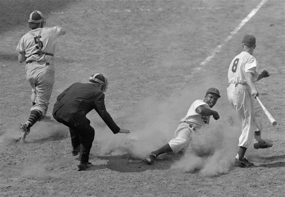 Jackie Robinson, Dodgers' second baseman, crosses home plate on a steal from third as Giants' catcher Walker Cooper (5) fires the ball to third base in the 7th inning of the Brooklyn - New York game at Ebbets Field, New York, July 4, 1948.  Dodgers won 13-12.  At right, is George Shuba, Dodger outfielder who was at bat.  Umpire is Scotty Robb. (AP Photo/Ray Howard) Photo: File
