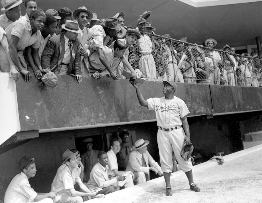 Jackie Robinson, first baseman of the Brooklyn Dodgers, returns an autograph book to a fan in the stands, during the Dodgers' spring training in Ciudad Trujillo, now Santo Domingo, in the Dominican Republic, on March 6, 1948. (AP Photo) Photo: File / AP1948