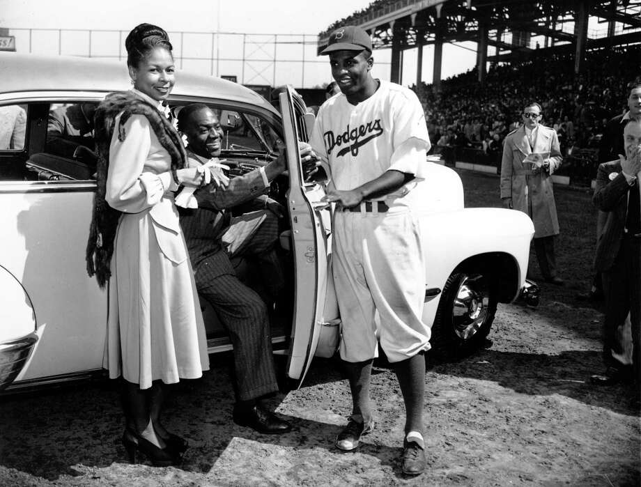 Jackie Robinson, the first baseman of the Brooklyn Dodgers, receives car keys from tap dancer Bill Bojangles Robinson in Ebbets Field in New York on Sept. 23, 1947.  The new automobile is presented to him by fans on Jackie Robinson Day as the Dodgers celebrate their newly-clinched National League Championship. At left is Robinson's wife, Rachel. Robinson also received a television set, a $500 watch, an inter-racial goodwill plaque and cash gifts. (AP Photo/Harry Harris) Photo: File