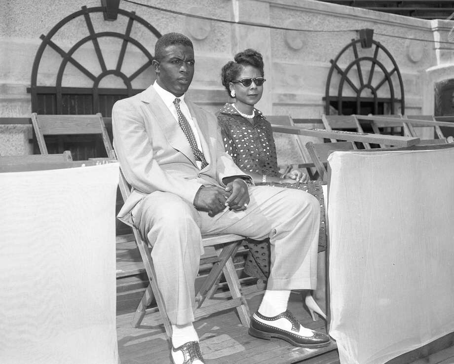 Jackie Robinson and his wife pose for photographs at the U.S. Open tennis tournament on September 1, 1951 in the Forest Hills neighborhood of Queens. Photo: Transcendental Graphics, File / 1951 Transcendental Graphics