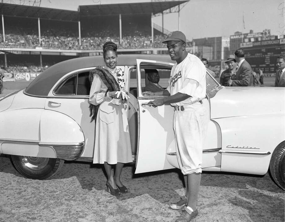 Jackie Robinson and his wife pose for photographs after a special awards ceremony in Ebbets Field, where Robinson was given a new car on  Jackie Robinson Day September 24, 1947 in Brooklyn. Photo: Transcendental Graphics, File / 1947 Transcendental Graphics