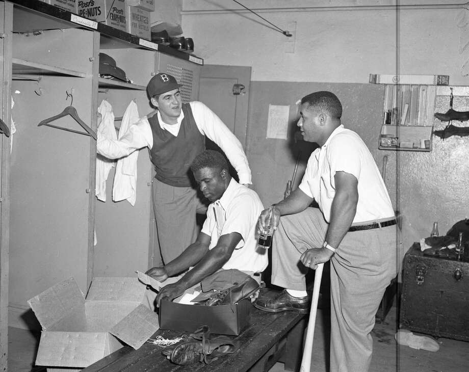 Jackie Robinson says goodbye to Brooklyn Dodger teammates Roy Campanella, right, and Preacher Roe in the clubhouse at Ebbets Field after the last game of the World Series in October, 1949 in the Brooklyn borough of New York City. Photo: Transcendental Graphics, File / 2006 Transcendental Graphics