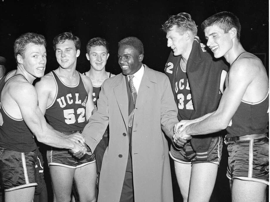 Jackie Robinson greets the members of the UCLA basketball team after defeating City College of New York on December 28, 1949 in New York City. Photo: Transcendental Graphics, File / 1949 Transcendental Graphics