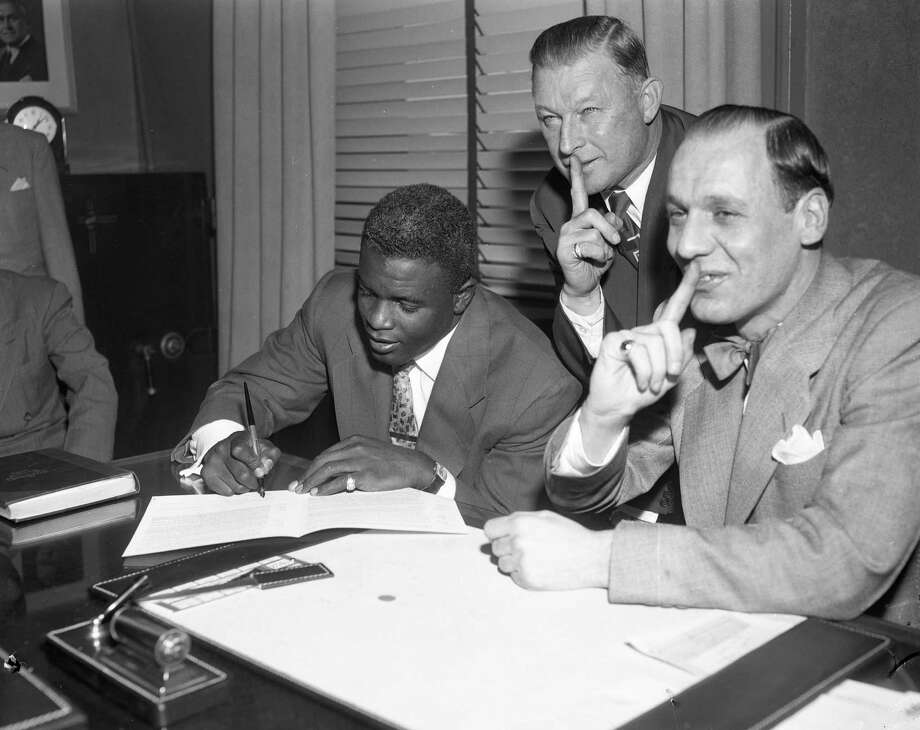 Jackie Robinson signs his contract for 1952 in the Brooklyn Dodger offices in Ebbets Field, with Leo Durocher, right, and Charlie Dressen looking on, January 10, 1952 in the Brooklyn borough of New York City. Photo: Transcendental Graphics, File / 1952 Transcendental Graphics