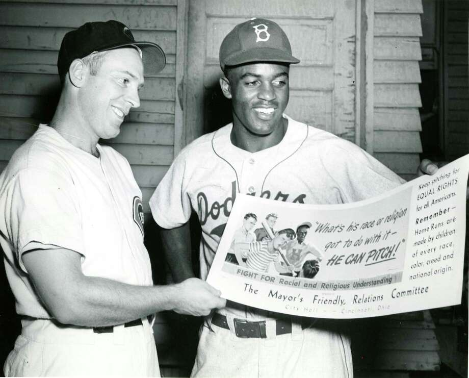 American baseball players Danny Litwhiler, left, of the Cincinnati Reds and Jackie Robinson of the Brooklyn Dodgers pose together as they smile and hold a poster form the 'Mayor's Friendly Relations Committee,' Cincinnati, Ohio, May 11, 1984. Photo: Cincinnati Museum Center, File / Archive Photos