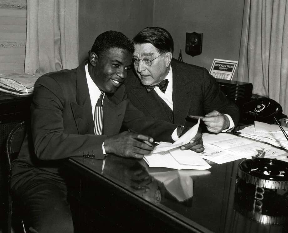 Jackie Robinson, left, and Branch Rickey share a joke during a contract signing session in the front offices of the Brooklyn Dodgers at Ebbets Field in Brooklyn in 1949. Photo: Transcendental Graphics, File / 2006 Mark Rucker/Transcendental Graphics