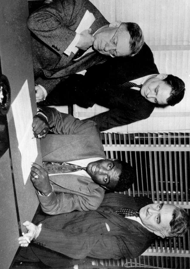 Jackie Robinson, first Negro player in the major leagues, signs with the Montreal Royals in Montreal October 23, 1945.  From left are: Royals president Hector Racine, Branch Rickey Jr., Robinson and Royals vice-president Romeo Gauvreau. (AP Photo) Photo: File
