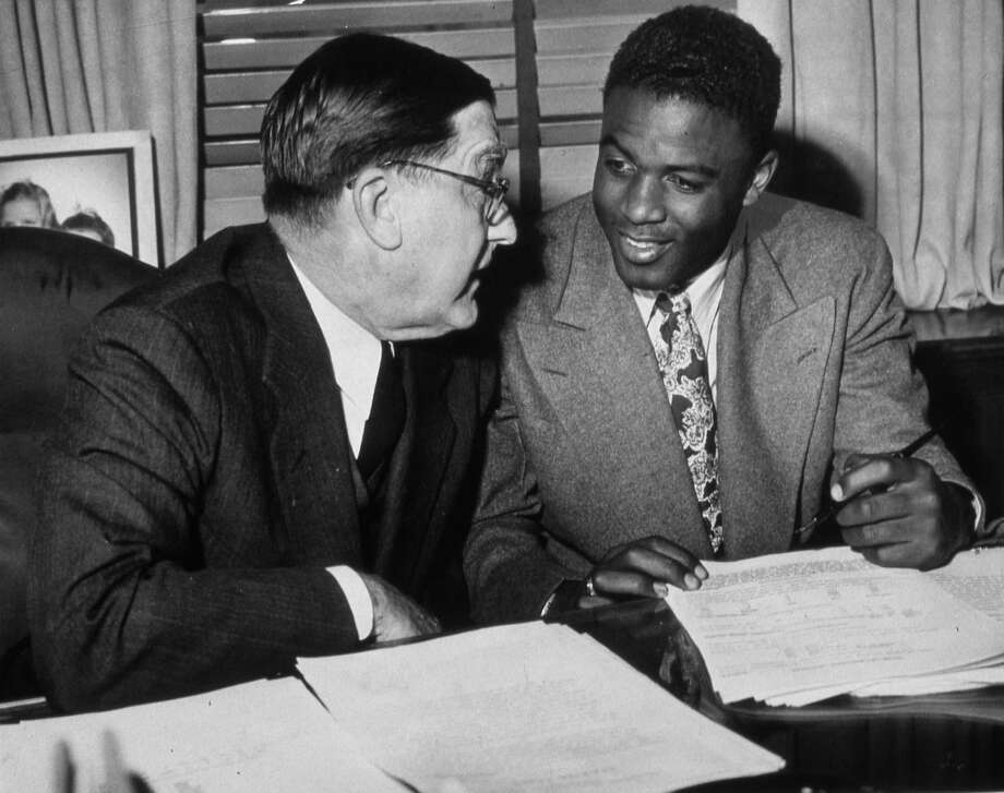 Branch Rickey speaks with Jackie Robinson as he signs his contract with the Brooklyn Dodgers for the 1948 season. Photo: Transcendental Graphics, File / 2006 Mark Rucker/Transcendental Graphics