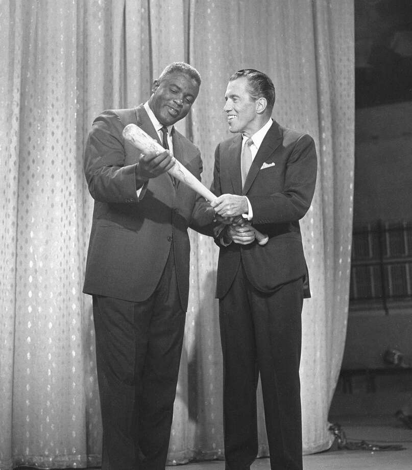 American professional baseball player Jackie Robinson, left, who famously broke the Major League Baseball color barrier in 1947, appears on the CBS television program 'The Ed Sullivan Show' with host Ed Sullivan, in New York, May 20, 1962. Photo: CBS Photo Archive, File / 2006 CBS WORLDWIDE INC.