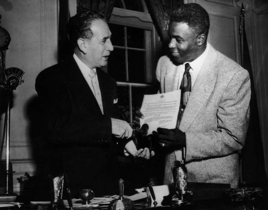 Vincent Impellitteri, Mayor of New York, sealing the proclamation announcing 'Urban League Week'. Brooklyn Dodgers second baseman Jackie Robinson holds the document in October 1952. Photo: Keystone, File / 2006 Getty Images