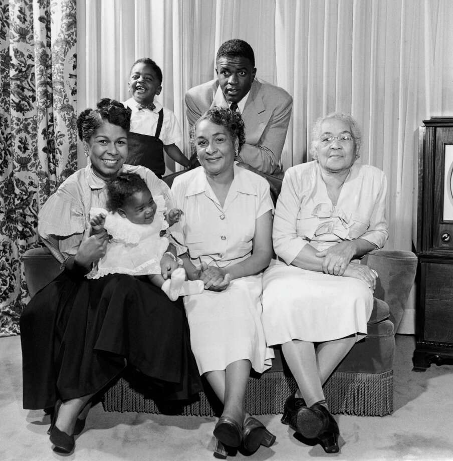 American baseball player Jackie Robinson of the Brooklyn Dodgers poses with his son Jackie Jr. behind the couch on which are seated his wife Rachel, his daughter Sharon, his mother Mallie and his grandmother, circa 1951. Photo: Archive Photos, File / 2006 Getty Images