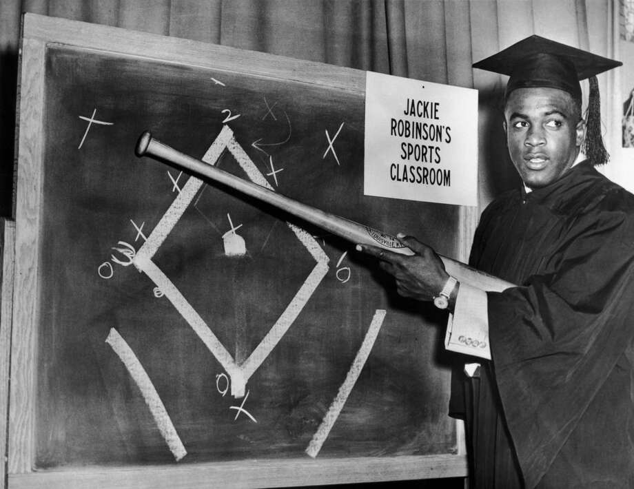 Brooklyn Dodger Jackie Robinson wearing a teachers outfit and mortarboard while illustrating baseball tactics on a blackboard in preparation for his 15 minute slot on television in December 1950. Photo: Keystone, File / 2006 Getty Images