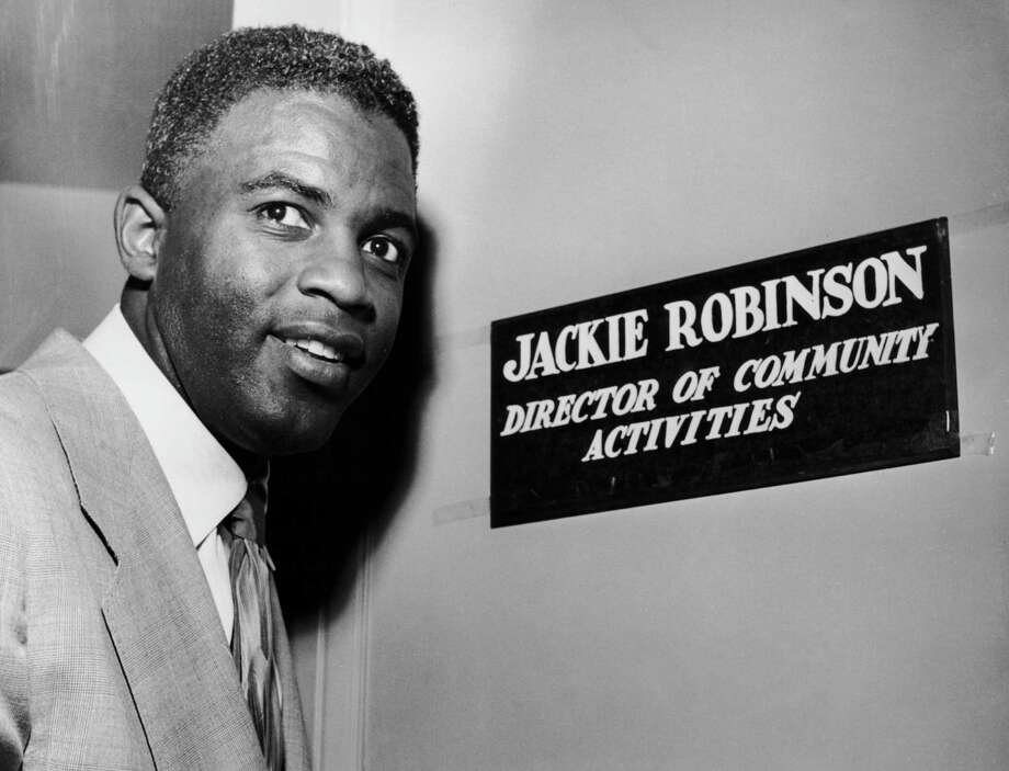 Jackie Robinson, Brooklyn Dodger's second baseman, outside the office that goes with his position of Director of Community Activities for NBC's New York outlets, WNBC and WNBT*TV, in February 1952. Photo: Keystone, File / 2006 Getty Images