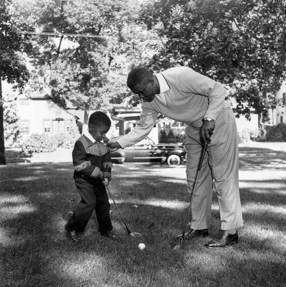 Jackie Robinson, the first African-American baseball player to play in the major leagues and to be inducted into the National Baseball Hall of Fame, playing golf with his son in 1951. Photo: Hulton Archive, File / Archive Photos