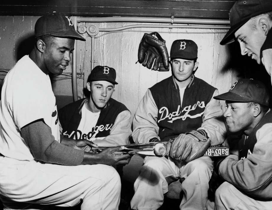 Baseball player Jackie Robinson showing his Brooklyn Dodgers team mates the silver bat he was been awarded for his National League .342 batting average, April, 21 1950. Left to right the Brooklyn Dodgers pitchers are Billy Loes, Preacher Roe and Don Bankhead. Photo: FPG, File / 2006 Getty Images