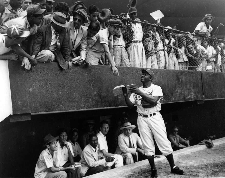 Jackie Robinson, first baseman for the Brooklyn Dodgers, signs autographs for fans in Havana, Cuba before a spring training game in March of 1947. Photo: Transcendental Graphics, File / 2006 Mark Rucker/Transcendental Graphics