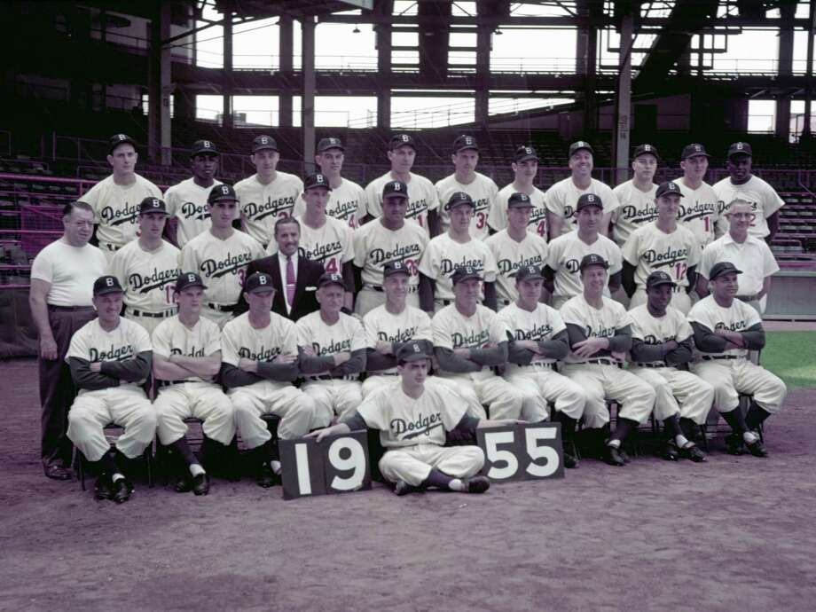 Members of the 1955 Brooklyn Dodgers poses for a portrait prior to a game on September 16, 1955 at Ebbets Field in Brooklyn, New York.  Pictured are: Front row, (L to R): George Shuba, Don Zimmer, Joe Becker, Jake Pitler (Coach), Walt Alston (Manager), Billy Herman (Coach), Pee Wee Reese, Dixie Howell, Sandy Amoros and Roy Campanella. Second row, (L to R): John Griffin (club houseman), Carl Erskine, Sandy Koufax, Lee Scott (Road Secretary), Roger Craig, Don Newcombe, Karl Spooner, Don Hoak, Carl Furillo, Frank Kellert and Doc Wendler (trainer). Third row, (L to R): Russ Meyer, Jim Gilliam, Billy Loes, Clem Labine, Gil Hodges, Ed Roebuck, Don Bessent, Duke Snider, John Podres, Al Rube Walker and Jackie Robinson. Batboy Charlie Digiovanni is in front. Photo: Kidwiler Collection, File / 1955 Diamond Images