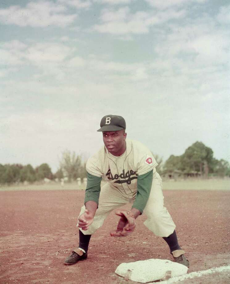 American professional baseball player Jackie Robinson of the Brooklyn Dodgers, dressed in a road uniform, crouches by the base and prepares to catch a ball, 1951. Throughout the course of his baseball career Robinson played several positions on the infield as well as serving as outfielder. Photo: Keystone, File / 2005 Getty Images