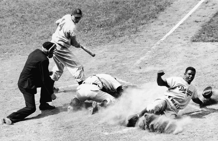 American baseball player Jackie Robinson of the Brooklyn Dodgers is tagged out by Cubs catcher Rube Walker after attempting to slide in and steal home base, Chicago, May 17, 1948. Gil Hodges is at bat. Photo: B Bennett, File / 2005 Bruce Bennett Studios