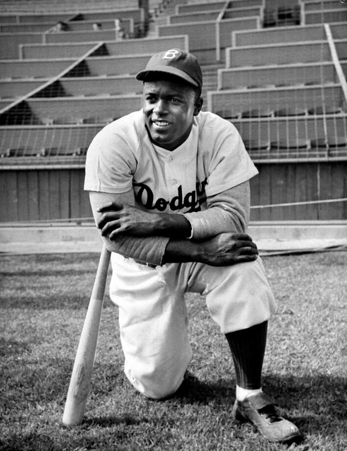 Baseball great Jackie Robinson in Brooklyn Dodgers uniform and leaning on bat as he kneels, during filming of The Jackie Robinson Story in 1950. Photo: Allan Grant, File / Time Life Pictures