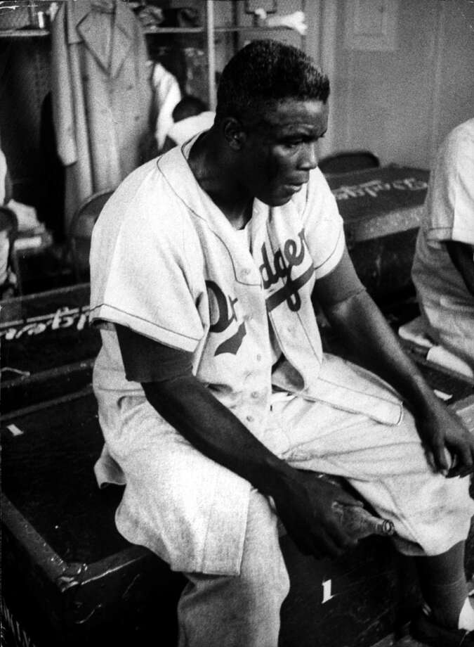Baseball Player Jackie Robinson looking exhausted and dejected in the locker room with an empty bottle of pop in his hand in 1955. Photo: Francis Miller, File / Time Life Pictures