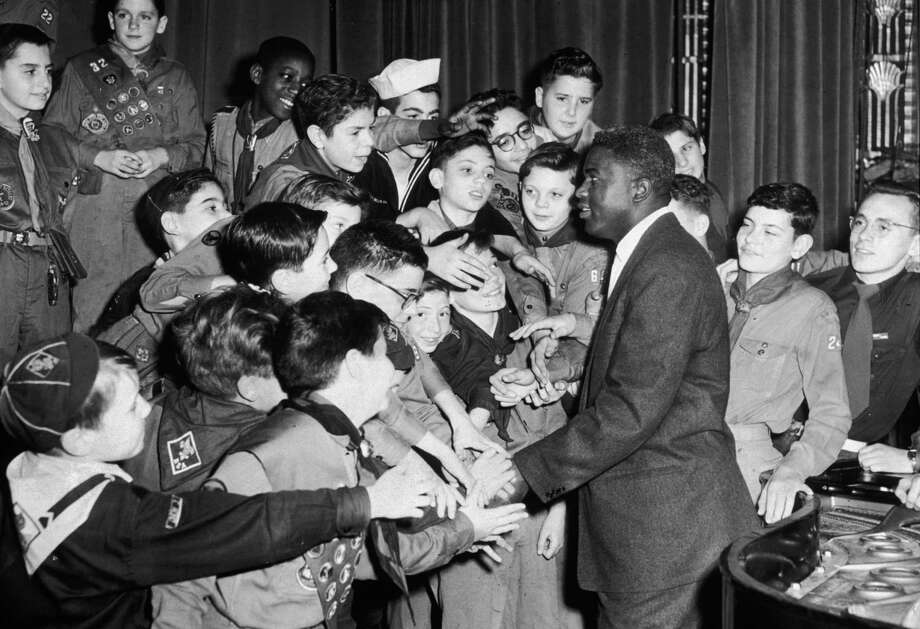 American baseball player Jackie Robinson, wearing a business suit, standing and smiling as he shakes hands with Boy Scouts and Cub Scouts in uniform at a Dawn Patrol Breakfast at the Grand Ballroom of the Waldorf-Astoria Hotel, opening the Greater NY Councils of the Boy Scouts 1953 Finance Campaign, New York City. Photo: Meyer Liebowitz, File / Archive Photos