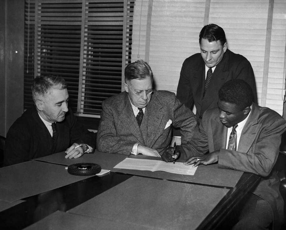 American baseball player Jackie Robinson signs a contract with the Montreal Royals, 24th October 1945. From left to right, Lieutenant Colonel Romeo Gauvreau, Hector Racine, Branch Rickey Jr. and Robinson. Photo: Archive Photos, File / 2006 Getty Images