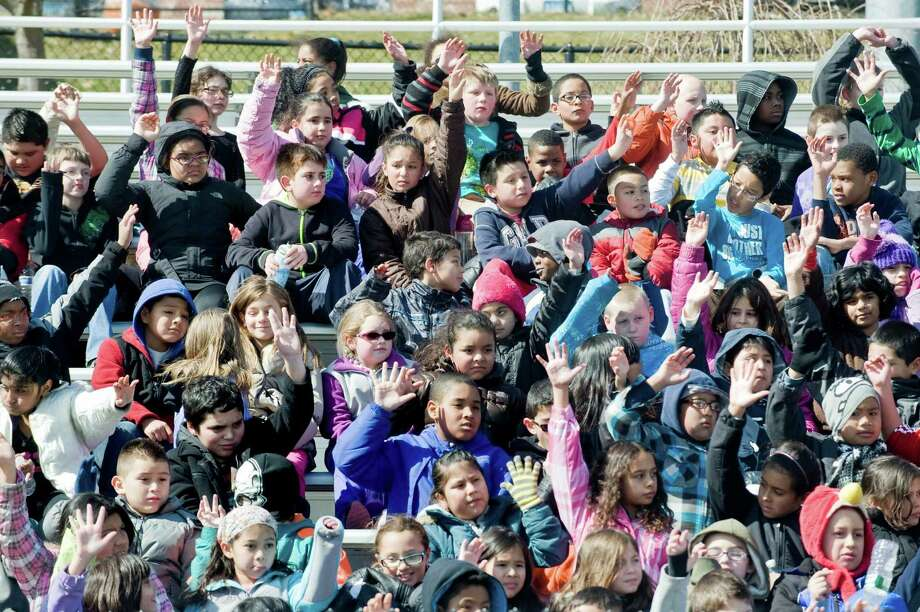 Third, fourth and fifth graders respond to exercise questions by raising their hands as they sit in the bleachers at the Danbury High School stadium during the KiDSMARATHON program. Over 500 kids are participating in the running and nutrition education program that enables KiDS to complete a full marathon (26.2 miles) by running approximately 3 miles per week. Tuesday, April 2, 2013 Photo: Scott Mullin / The News-Times Freelance
