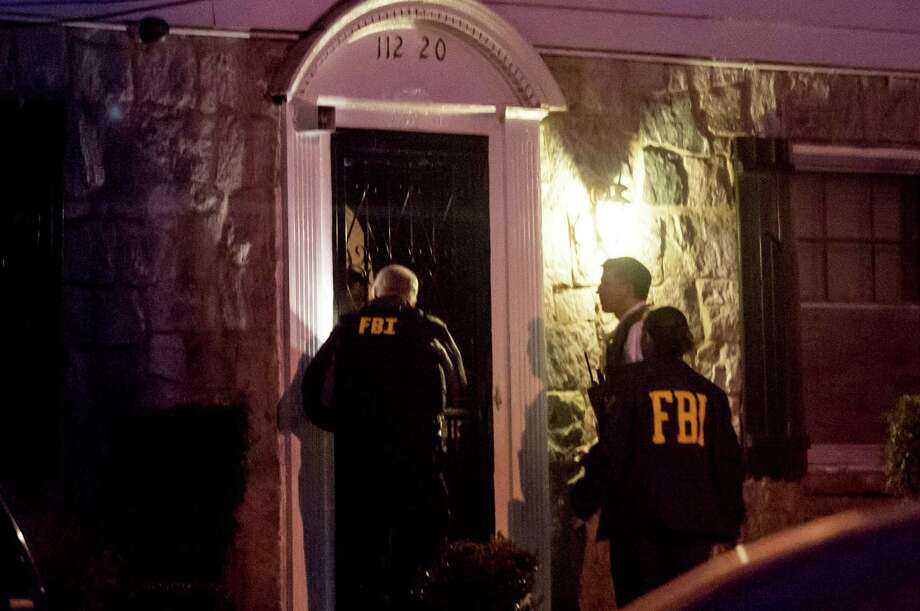 Members of the FBI raid the home of Sen. Malcolm Smith (D-N.Y.), in New York, April 2, 2013. Smith, a contractor and real estate developer who rose to become the first black president of the State Senate, and City Councilman Daniel Halloran III were arrested early Tuesday on charges of trying to illicitly get Smith on the ballot for this year's mayoral race in New York, according to federal prosecutors. (Robert Stolarik/The New York Times) Photo: ROBERT STOLARIK / NYTNS