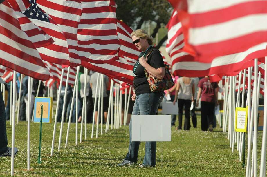 JuleeAnna Lee, an Algebra III teacher at La Porte High School, checks out the signs in the Healing Field, a forest of 1,547 flags covering an area of two football fields at Nessler Park in Texas City. Lee was accompanying members of the La Porte High School Shattered Dreams team to the March 18 Healing Field ceremony. Each flag represents a person who was killed in an alcohol-related motor-vehicle crash. JuleeAnna Lee, an Algebra III teacher at La Porte High School, checks out the signs in the Healing Field, a forest of 1,547 flags covering an area of two football fields at Nessler Park in Texas City. Lee was accompanying members of the La Porte High School Shattered Dreams team to the March 18 Healing Field ceremony. Each flag represents a person who was killed in an alcohol-related motor-vehicle crash. Photo: Jerry Baker, Freelance