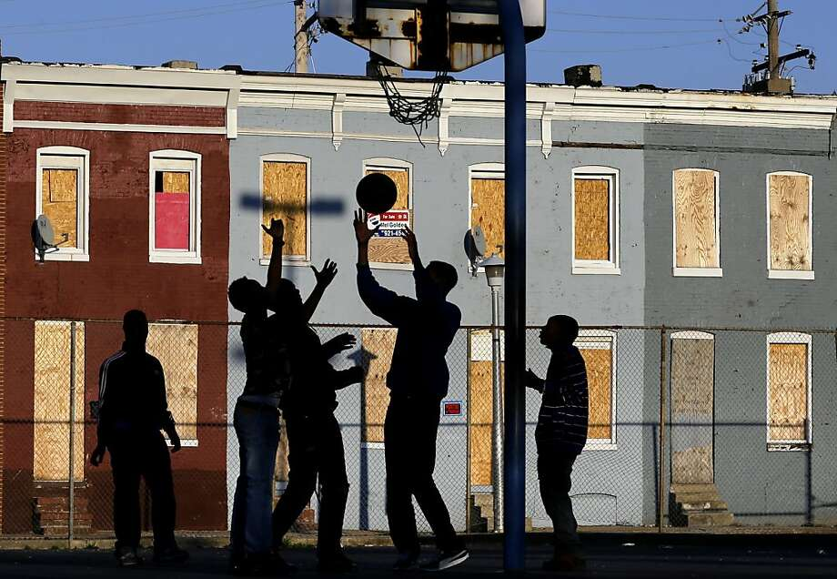Children play basketball at a park near blighted row houses in Baltimore, Monday, April 1, 2013. Baltimore is far from the worst American city for poverty, but it faces all the problems of cities where vast numbers of the poor now live. The U.S. Census Bureau puts the number of Americans in poverty at levels not seen since the mid-1960s, while $85 billion in federal government spending cuts that began last month are expected to begin squeezing services for the poor nationwide.  Photo: Patrick Semansky, Associated Press